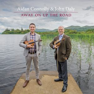 Image for Album Cover (2019) - showing Aidan Connolly and John Daly standing by the edge of Lough Gill and each holding a fiddle